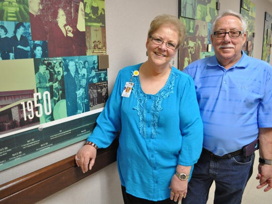 Twins Joy Aldret Hirsch and Roy Aldret stand in Christus St. Frances Cabrini Hospital next to a collage of photos taken at the hospital in 1950, the year they were born.