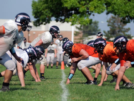 The offense lines up against the defense Monday, Aug 17, during football practice at Marine City High School.