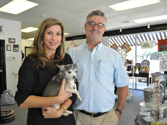 Allen Smith and wife Lizette Smith, Hurricane Katrina transplants, pose with their dog, Arrow, which was rescued in New Orleans after the storm. They are shown in Southern Chic gift store, which Lizette co-owns.