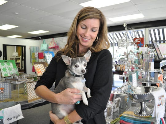 Lizette Smith, co-owner of Southern Chic in Alexandria and a Hurricane Katrina transplant, holds her dog, Arrow, which was rescued in New Orleans after the storm.
