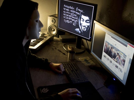 A masked hacker, part of the Anonymous group which briefly knocked the FBI and Justice Department websites offline in retaliation for the U.S. shutdown of file-sharing site Megaupload, is a shadowy group of international hackers with no central hierarchy. On the left screen, an Occupy mask is seen.