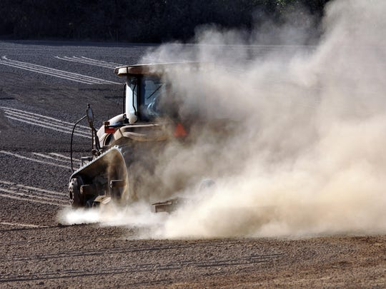 A tractor sends up plumes of dust as it plows in bone-dry fields off Old Stage Road on Wednesday in Salinas during the early September heat wave.