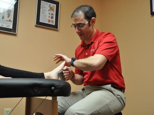 Justin Feldman works on a patient's foot.