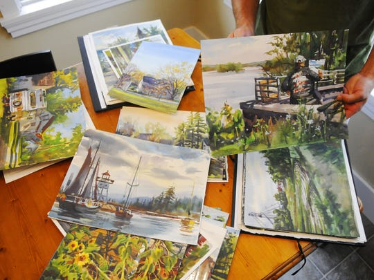 Watercolorist Dan Mondloch shows some of his plein air paintings at his home. They will be on display later this month at the Paramount Visual Arts Center.