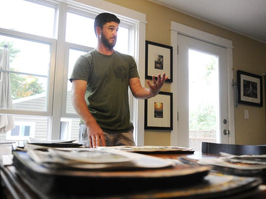 Watercolorist Dan Mondloch shows some of his paintings at his home Monday in the Seberger neighborhood. He has spent the past year, with the help of a grant, on plein air paintings.