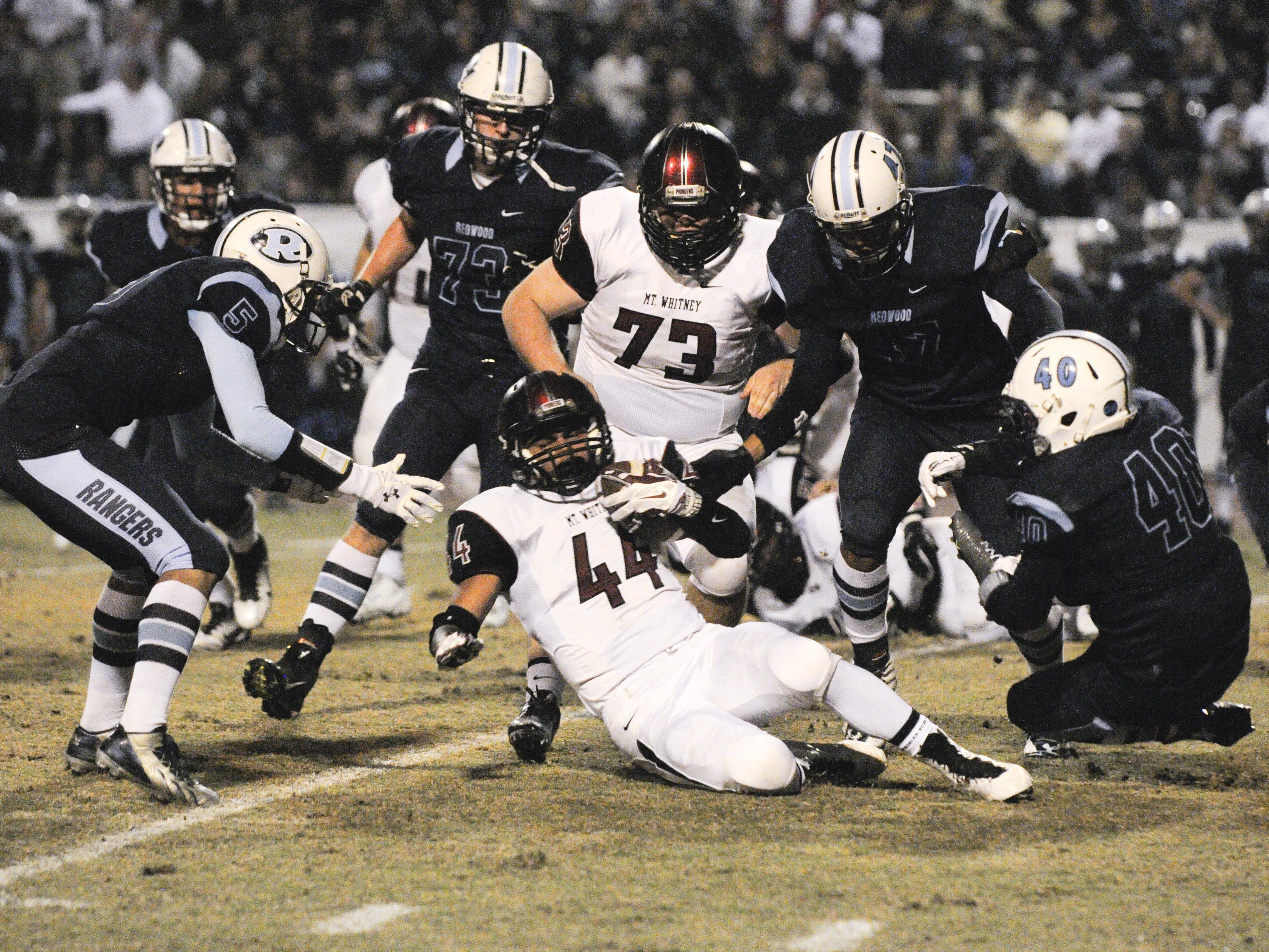Mt. Whitney running back Michael Ingram holds onto possession in the 60th annual Cowhide game at Giant Chevrolet-Cadillac Mineral King Bowl last season. Redwood won 41-14.