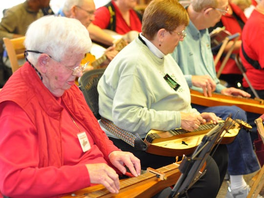From left, Elaine Johnson, of Union, and Paula Williams and Tom Williams, of Cincinnati, play their dulcimers for a crowd of about 50 at the Florence branch of the Boone County Library Sunday, Dec. 13. All are are members of the Hills of Kentucky Dulcimers, a group of more than 150 members.