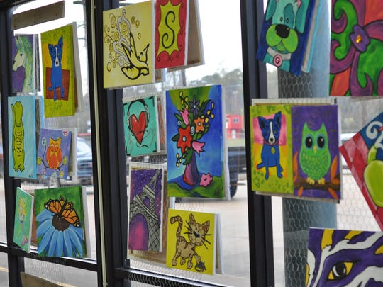 Brightly colored art decorates the walls of QuirkyArtz and serve as examples of what customers can come paint themselves with the help of owner Nan Burns. Examples of simpler drawings geared toward children who want to come paint hang on the window.