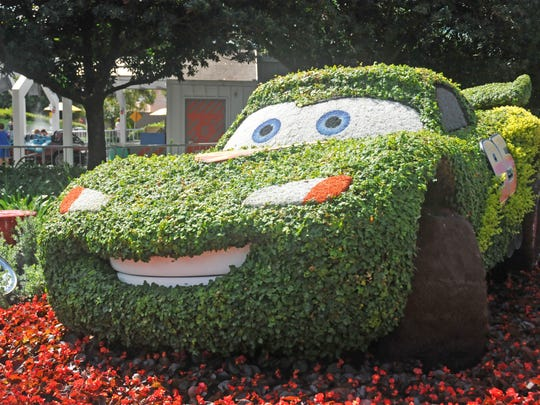 "A bush arrangement looks like Disney's ""Cars"" character Lightning McQueen near Test Track as part of Epcot's Flower and Garden Festival."