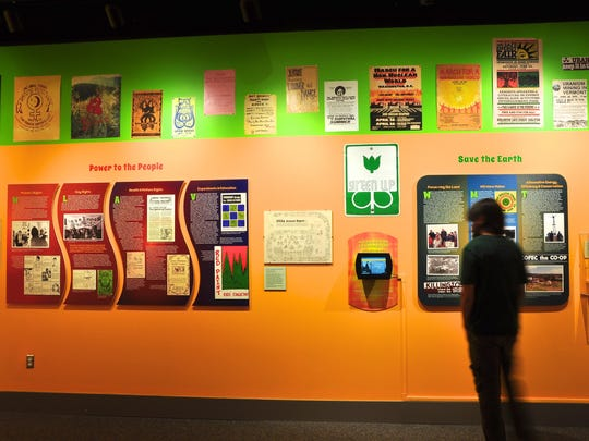 """A visitor to the Vermont History Center in Barre looks at the exhibit """"Hippies, Freaks and Radicals: 1970s Counterculture in Vermont."""""""