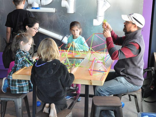 A family taking part in one of the hands-on STEM activities in the maker space at ECHO Leahy Center for Lake Champlain in 2017.