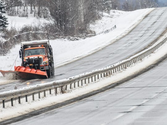 A plow removes snow from the shoulder of Airport Road in December 2013.