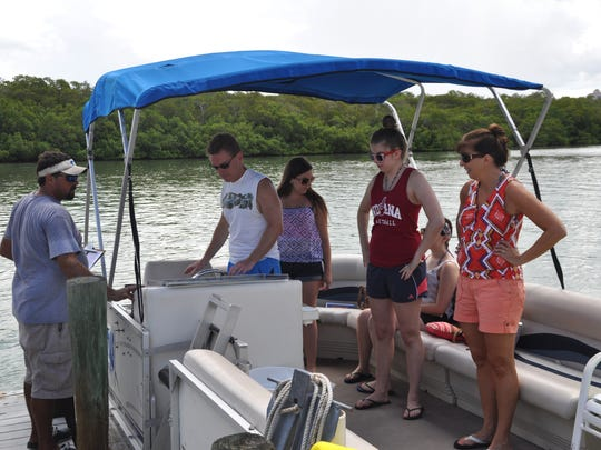 Andy King, manager of Bonita Boat Rentals, shows the Maughan family a few things on the rental boat before sending them out for an afternoon on the back bays of Estero.