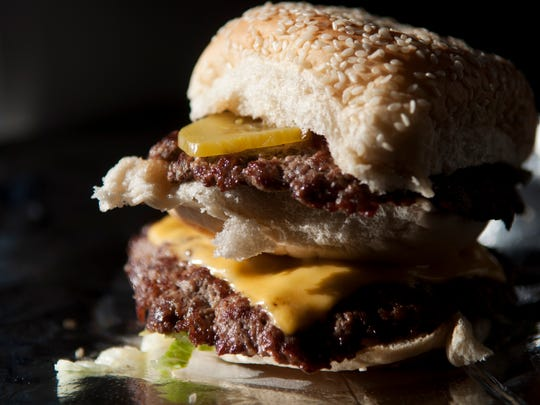 "The ""High Burger"" from BurgerQue is made with two handmade burger patties, three buns, one piece of cheese, lettuce, pickles, mayonaise, ketchup and mustard."
