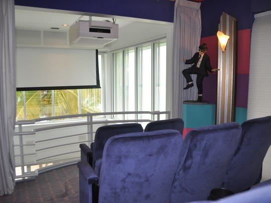 The theater overlooks the two story living room. Blackout shutters come down to darken the area and a screen lowers for movie viewing.