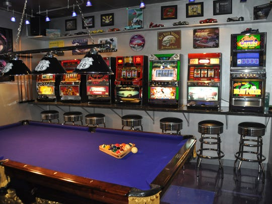 A game room features casino like slot machines along with a pool table.