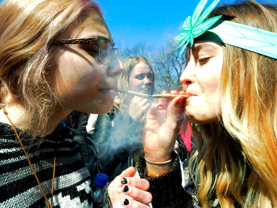 Participants smoke during the annual Hash Bash at the