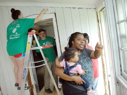 """Sonja Frazier holds her 1-year-old daughter, Ilia, and talks with her mother, Martha Nixon, about their home as volunteers paint and rebuild damaged areas to the house. Volunteer Chelsea Angelo paints above a doorway, and volunteer captain Fabian Bedne looks through as they talk. Rebuilding Together Nashville, along with 150 volunteers, hosted a """"makeover event"""" providing free critical repairs and modifications to homes of five low-income families in an East Nashville neighborhood April 18, 2015."""