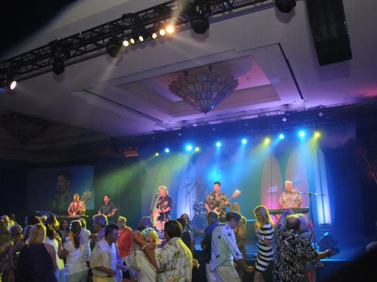 Dancers with Dean Torrece and Surf City AllStars on stage.