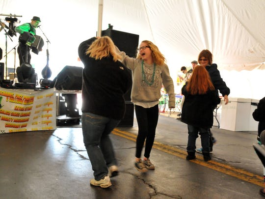 Dakota Eckerman, 11, of Oak Harbor, laughs as she dances with her mom, Missy Bolanis, of Port Clinton, to the Might McGuiggans at McCarthy's 10th anniversary tent event in downtown Port Clinton.