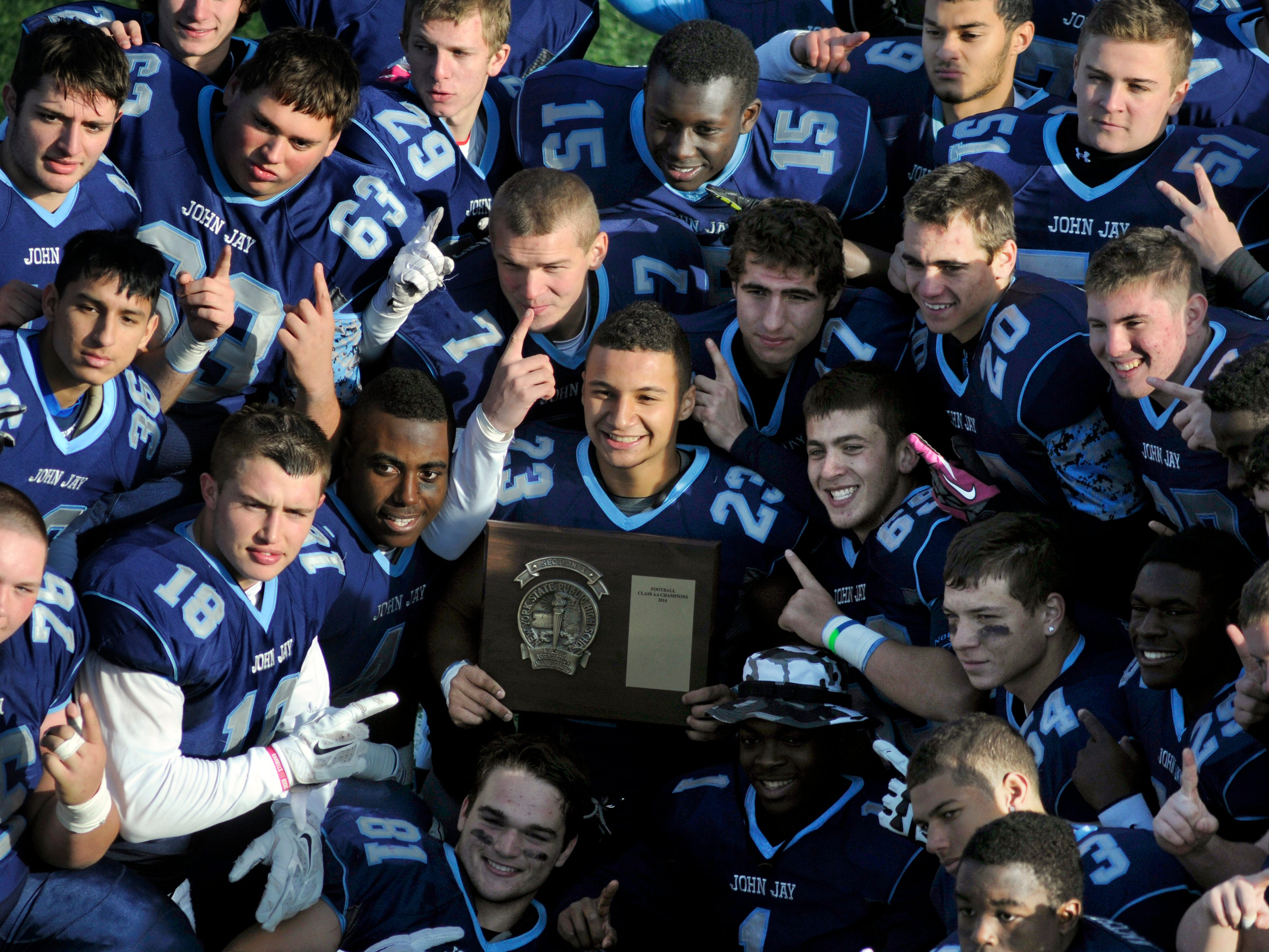 The John Jay High School football team holds the Section 1 Class AA Championship plaque on Nov. 8, 2014 in Mahopac.