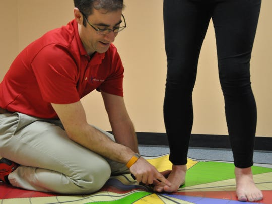 Justin Feldman shows a patient how to develop motor control for better toe extension in this file photo.