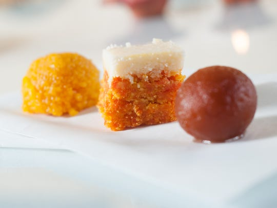 Sweets are served for Diwali because happy moments are celebrated with sweets. From left: laddu chickpea flour balls soaked in honey, a milk solids and cardamom bite made to resemble carrot cake, and gulab jamun dumplings dipped in rose water syrup.