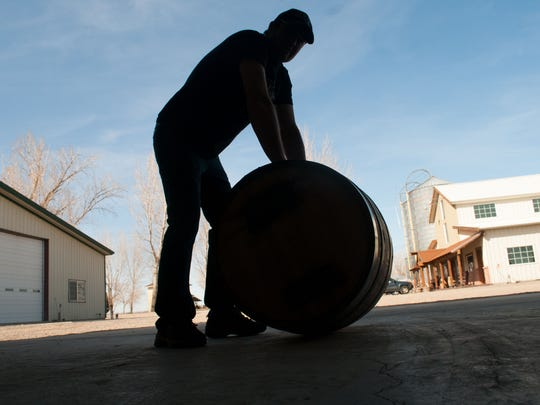 Colby Frey rests while transferring aging barrels at Frey Ranch Distillery. The distillery building is at right.