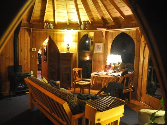 The main room of the Hobbit House rental shows off how all doors and windows taper on top to pointy arches. Each room's conical ceiling is topped by a dome-shaped skylight.