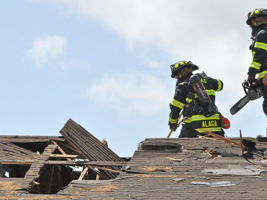 Salinas firefighters ventilate a roof on Bridge Street as part of a training exercise on Monday. The buildings will be demolished to make way for senior housing.