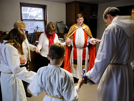 The Rev. Greg Mastey leads a prayer before the start of his Palm Sunday Mass.
