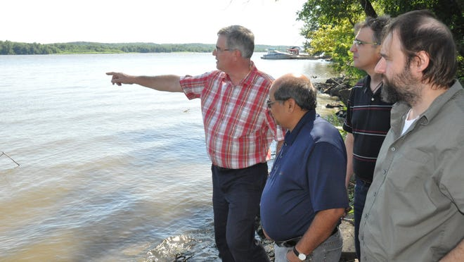 Doug Schnoebelen, left, explains early-20th-century freshwater mussel production along the Mississippi River at Muscatine on Wednesday.