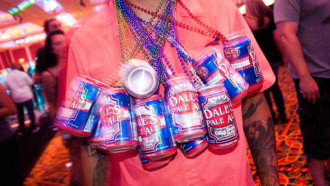 A reveler at Canfest 2014 works a beer can necklace. Canfest 2015 includes about 40 to 50 brewers offering more than 100 canned beers.