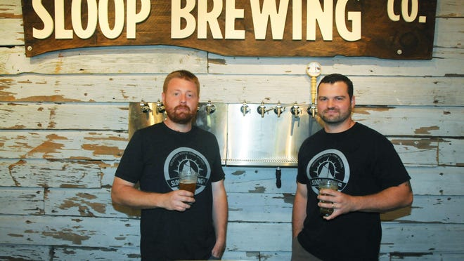 Adam Watson, left, sales and business manager, and Justin Taylor, head brewer and product manager, stand behind the bar of Sloop Brewing Co. in Elizaville in this file photo.