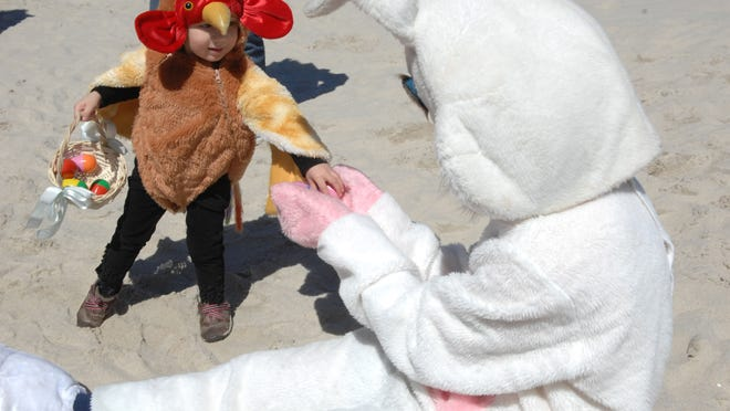 Camillia Huetter (2) of Belmar meets with the Easter Bunny during the Palm Sunday Easter Egg Hunt on the beach in Seaside Heights.