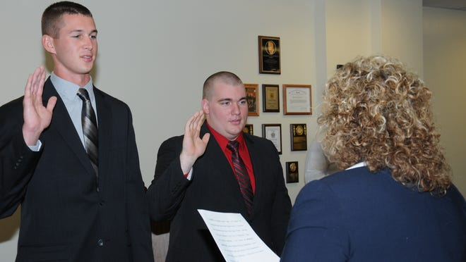 Safety-Service Director Lori Cope swears in new Mansfield police officers Matt Davis, left, and Thayne Telquist.