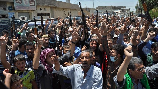 A plan to divide Iraq into three sectarian segments could avoid scenes like this, Shiite mourners in the village of Taza Khormato chanting slogans after Sunni militants handed over 15 decomposing bodies.