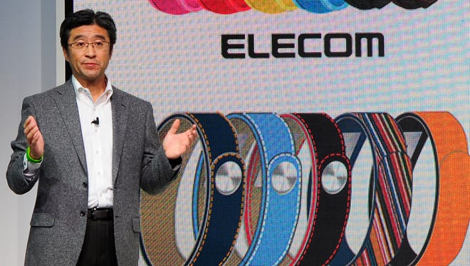 President and CEO of Sony Mobile Communications Kunimasa Suzuki presents the Smartband device during the Mobile World Congress, the world's largest mobile phone trade show in Barcelona, Spain, Monday, Feb. 24, 2014.