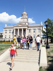 Students walk through the Pentacrest during the first day of class at the University of Iowa on Monday, Aug. 20, 2012