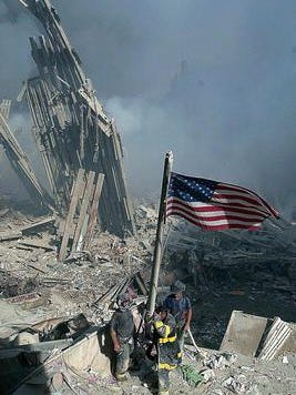 Three New York City firefighters raise the American flag from the rubble of the World Trade Center, Tuesday, Sept. 11, 2001.