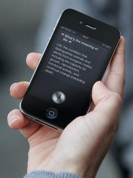A man uses 'Siri' on the iPhone 4S , the first phone to use the app voiced by Susan Bennett.