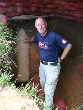 Jim Harris stands next to a 750-pound bomb found under a house in rural Laos.