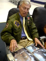 Retired Navy Capt. Flack Logan looks over pictures