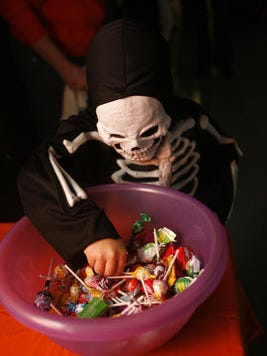 A little boy wears his skeleton costume as he picks out a piece of candy at a Halloween party.