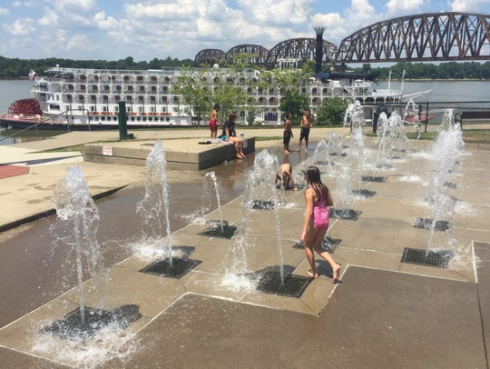Kids play in the riverfront water feature as the massive