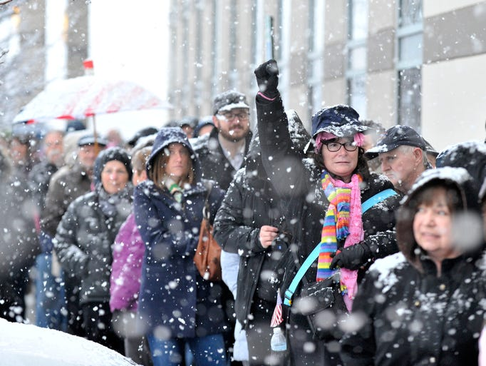 Hundreds wait outside the building in the snow as only