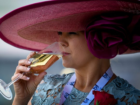 A woman wearing a colorful hat sips champagne on Derby