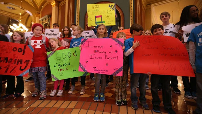 A group of children and parents carry signs through the state capitol on Wednesday, March 25, 2015 during a rally for state education funding.