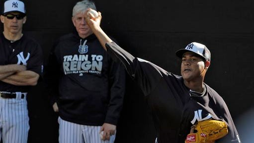 New York Yankees pitcher Ivan Nova, right, throws in the bullpen as manager Joe Girardi, left, and pitching Larry Rothschild, center, look on during a spring training baseball workout Monday, Feb. 22, 2016, in Tampa, Fla. (AP Photo/Chris O'Meara)