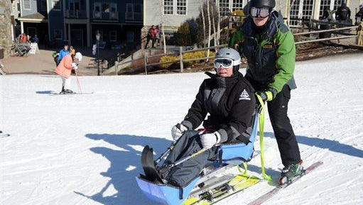 With the help of Clarlie Reutemann, Don Tallman of Glenville, N.Y., gets ready to ride the chairlift after coming down in a bi-ski at Jiminy Peak in Hancock, Mass., on March 6, where STRIDE Adaptive Sports provided a weekend of lessons to disabled service men and women who have sustained permanent injuries as a result of conflicts in Iraq and Afghanistan. This weekend was the first time Tallman ever went skiing in his life.